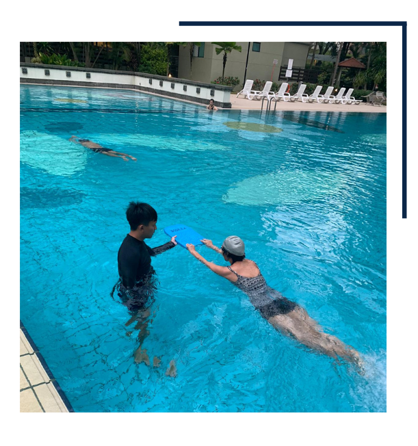Male Swimming Instructor With Adult Student